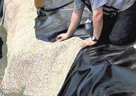 Teichbau Schritt 5: Die Folie wird in der Teichgrube verlegt.