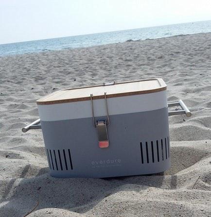 Der Everdure Cube in grau steht am Strand, im Hintergrund das Meer.