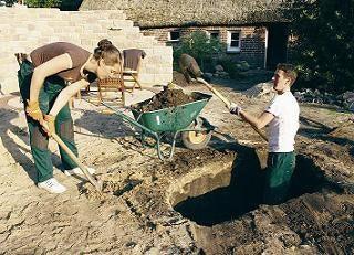 Die Teichgrube wird mit Schaufeln ausgehoben.