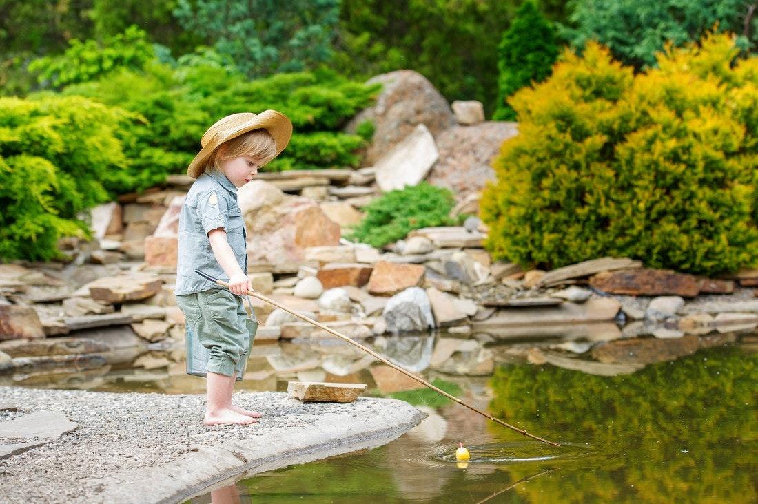 Kleiner Junge mit Strohhut angelt im Teich.