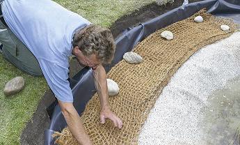 Teichbau Schritt 6: Mit Steinfolie und Böschungsmatten wird der Randbereich naturnah gestaltet.