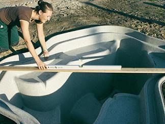 Die eingesetzte Teichschale wird mit Hilfe von einer Latte und einer Wasserwaage gerade positioniert.