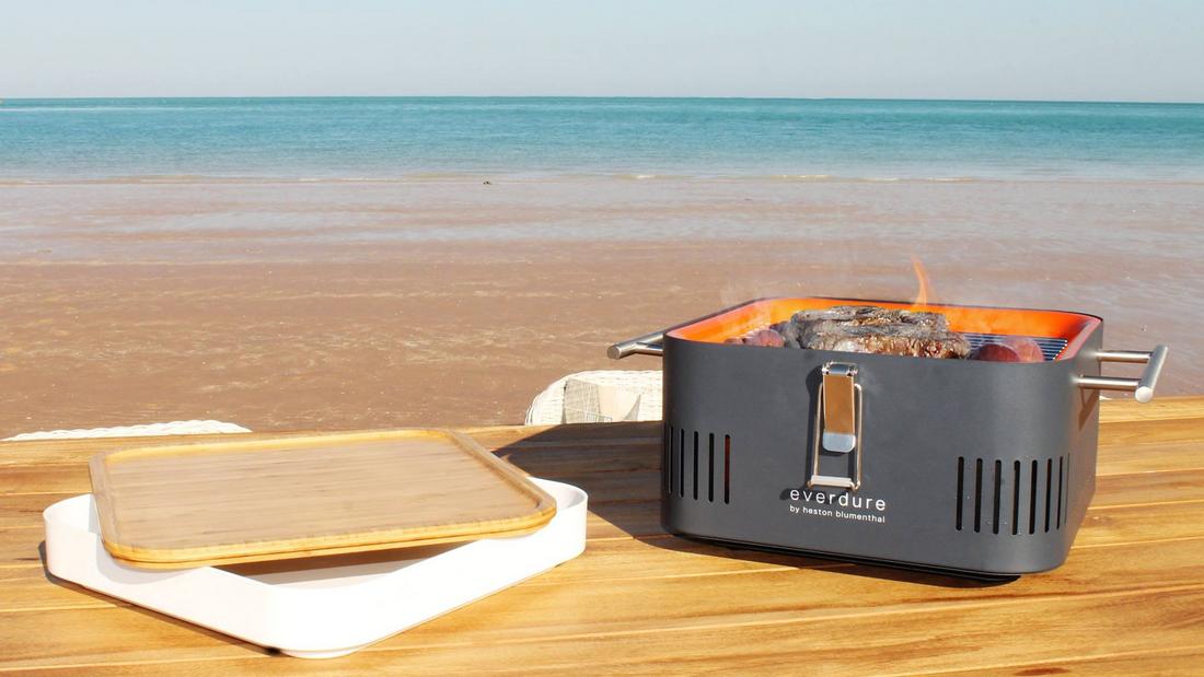 Everdure Cube in Schwarz steht direkt am Strand auf einem Holztisch, der Strand und das Meer sind im Hintergrund