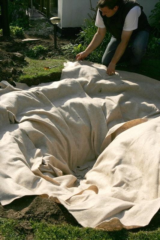 Die Teichgrube wird komplett mit Teichschutzvlies ausgekleidet.