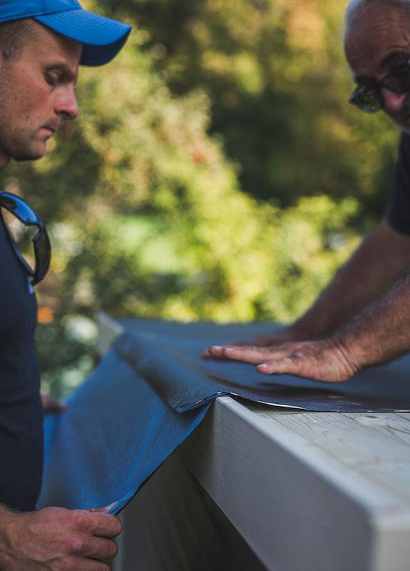 Die Dachbahnen werden vorsichtig, Stück für Stück aufgeklebt.