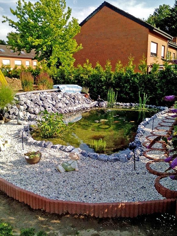 Der Rand des Teiches wird mit Kieselsteinen und Pflanzen gestaltet.