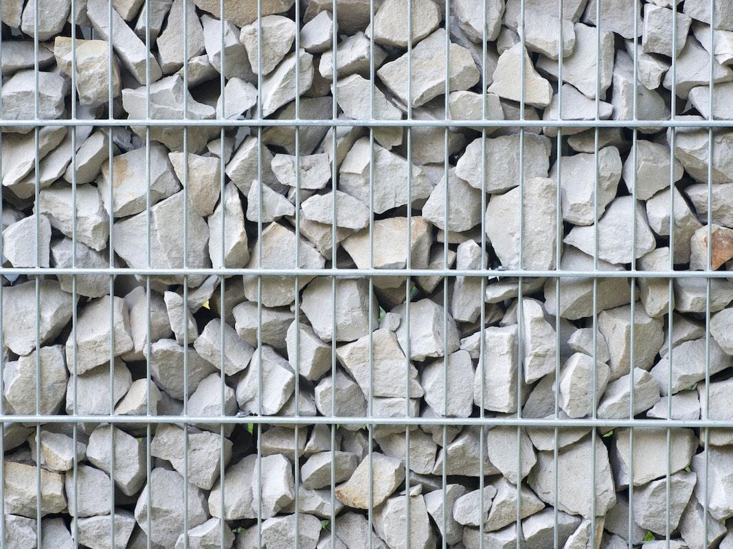 Gabione mit weißen steinen in kleinen Bruchstücken