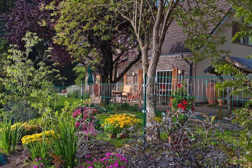 Gittermattenzaun an schön bepflanzter Grundstücksgrenze