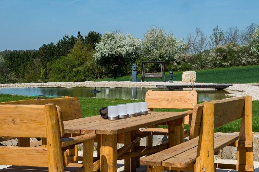 Großer Gartenteich mit Holztisch-Garnitur, Steg und Hollywoodschaukel.
