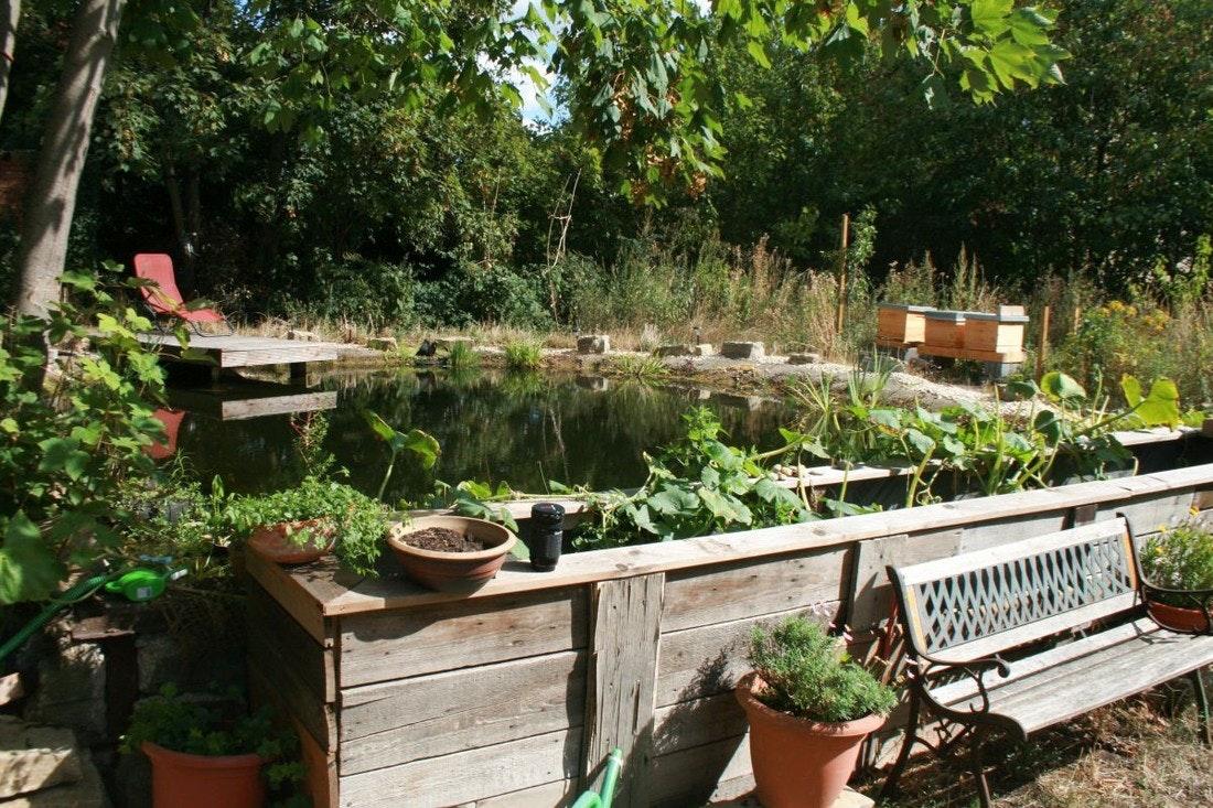Ein selbstgebautes Hochbeet grenzt direkt an den Teich