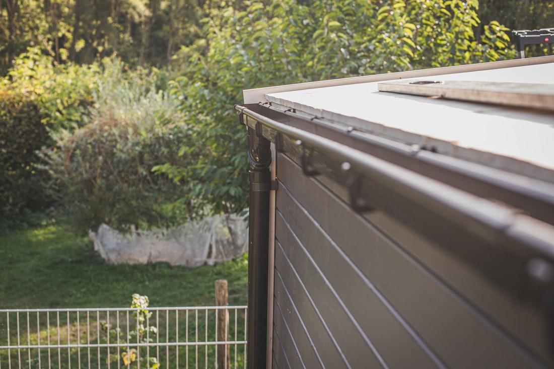 Die Dachrinne hat ein leichtes Gefälle nach einer Seite, an der ein Fallrohr angebracht ist.