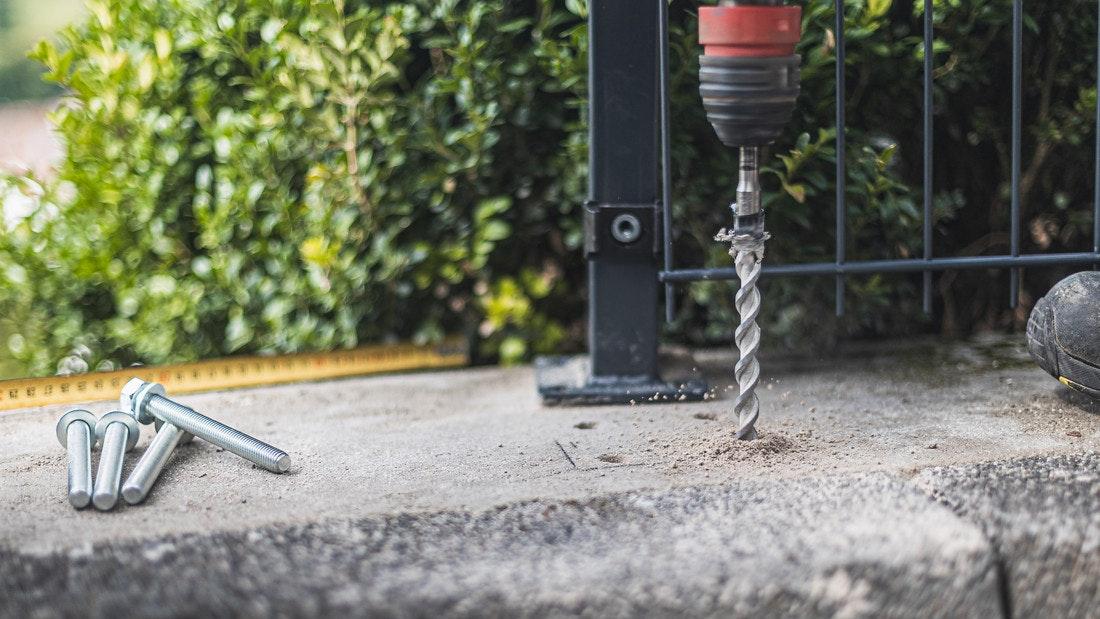 Die Löcher für die Schrauben werden in den Betonboden gebohrt