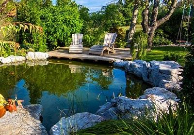 Runder Gartenteich von großen Steinen eingefasst mit Holzterrasse und zwei gemütlichen Holzliegen.
