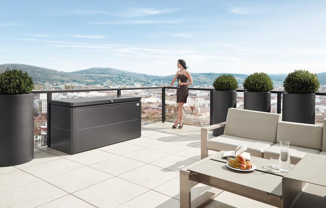 Frau auf Terrasse mit Gartengerätebox