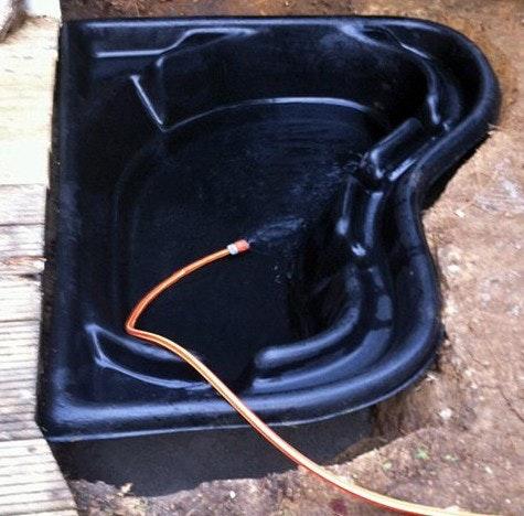 Teichschale aus PE wird mit einem Gartenschlauch mit Wasser gefüllt.