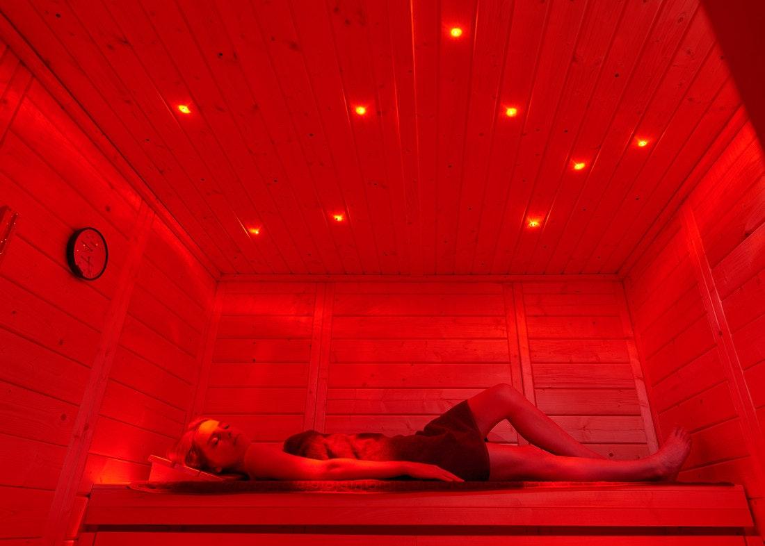 Eine Frau entspannt auf einer Saunabank mit rotem Licht und Sternenbeleuchtung