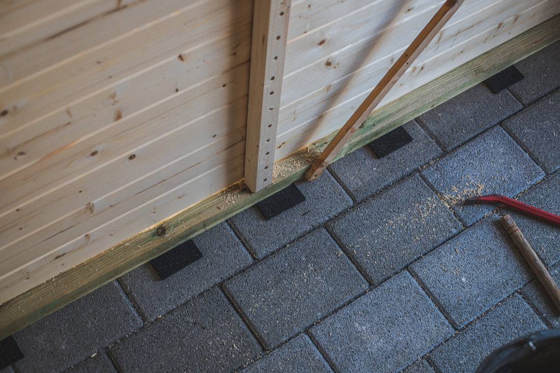 Nachdem das Gartenhaus an seine endgültige Position gesetzt wurde, werden Pads aus Gummigranulat untergelegt.