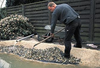 Teichbau Schritt 9: Der Ranbereich wird mit Kieselsteinen gefüllt und mir einer Schaufel verteilt.