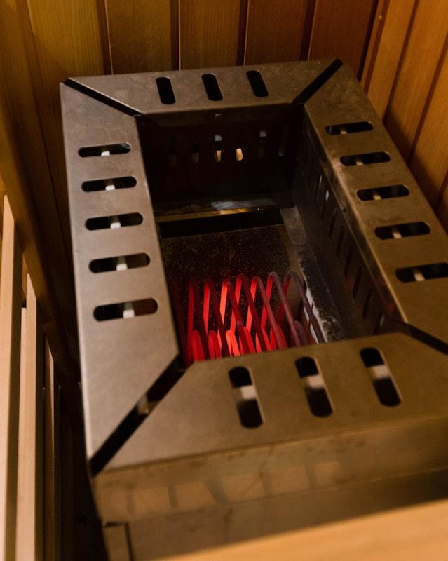 Glühende Heizstäbe in einem alten Saunaofen. Der Ofen sollte nie betrieben werden, wenn keine Steine darin aufgeschichtet sind!