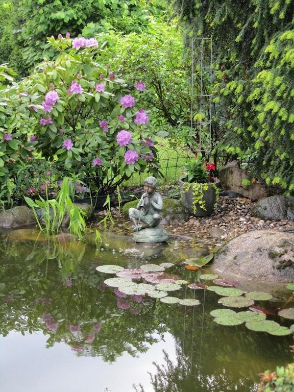 Flötenspieler Statue am Teich