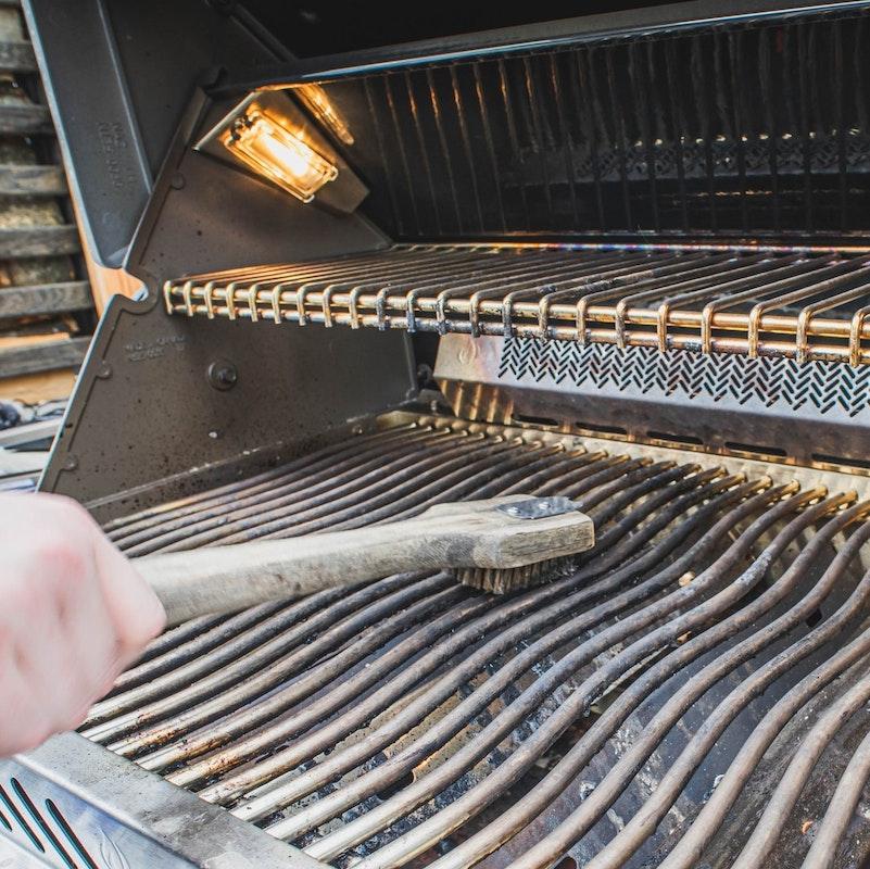 Reinigung des Grillrosts mit einer Grillbürste