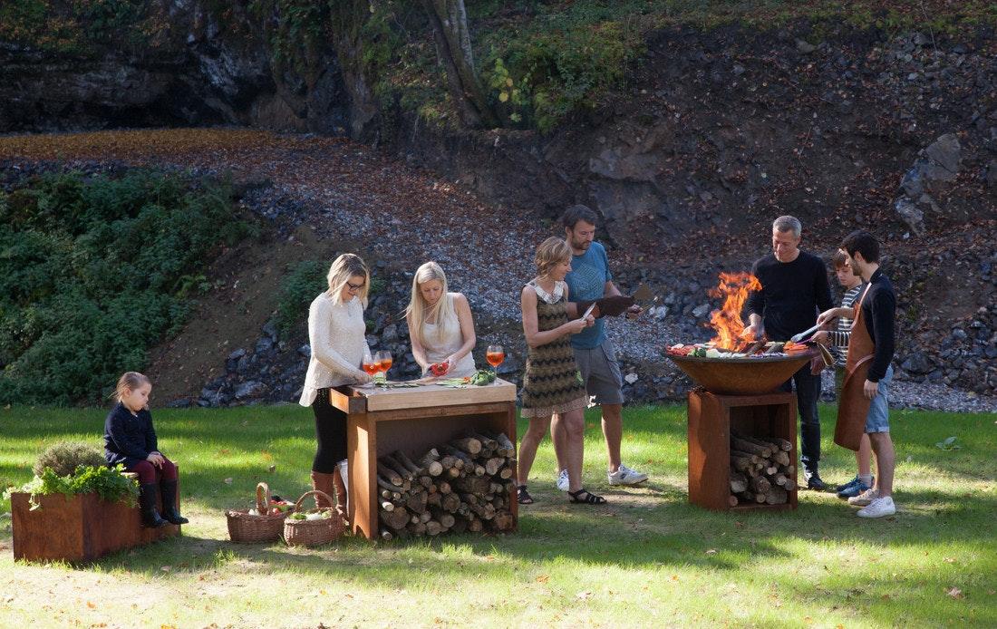Eine Grillparty im Grünen gelingt mit Kocheinheit und Zubehör von Ofyr wie dem Butcher Block und der Garden Bench besonders gut