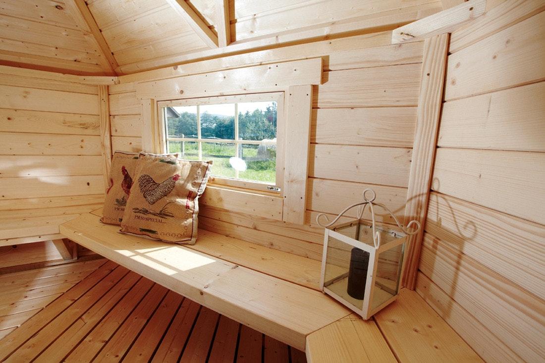 Sitzflächen in einer Grillkota mit Blick durch das Fenster