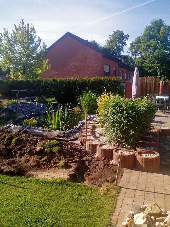 Der Koiteich passt sich perfekt an die Terrasse an, das Blumenbeet neben dem Teich ist noch unbepflanzt.