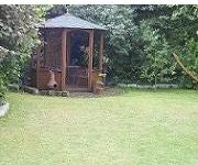 Grüne Rasenfläche und Pavillon eingegrenzt von Hecken