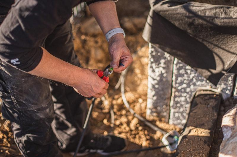 Unser Experte schließt kürzt das Kabel der Gartenbeleuchtung auf die richtige Länge