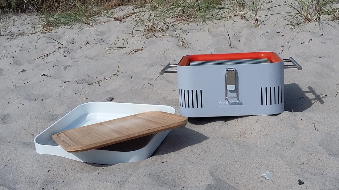 Cube Grill steht vor einer Düne am Strand, die weiße Aufbewahrungsbox und das Schneidebrett aus Bambus liegen daneben