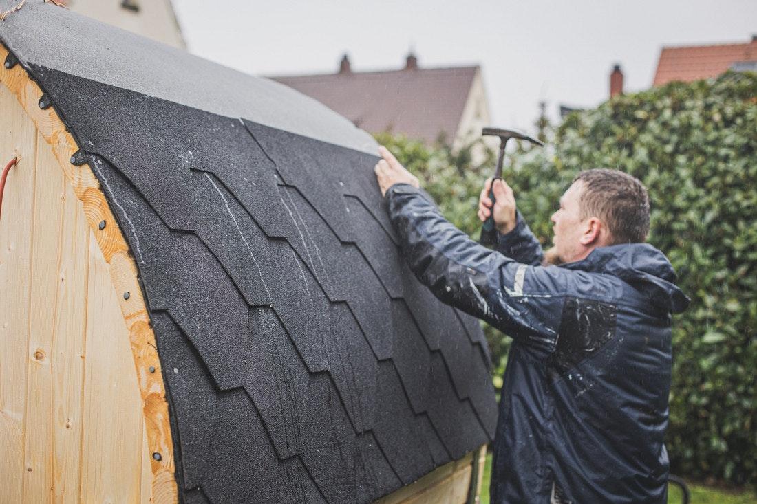 Über die Dachplane werden Dachschindeln angebracht, die der Fasssauna ihren Look geben.