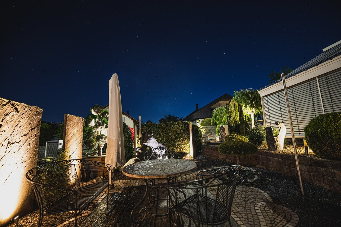 Eine gelungene und atmosphärisch ausgeleuchtete Terrasse im Dunkeln